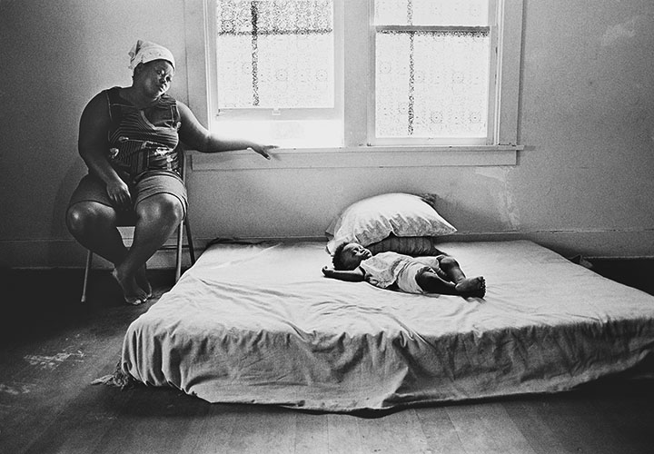 Gail Price with her 8 month old daughter, Ailcher napping on the one bed the family of six share. ©Eli Reichman, All Rights Reserved.  ©